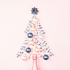 Christmas tree made of bauble decoration on pink background with champagne. Minimal New year concept.