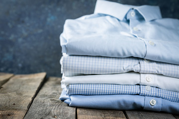 Stack of male folded shirts on rustic background, copy space
