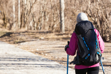 Woman wearing a backpack hiking on a rural road