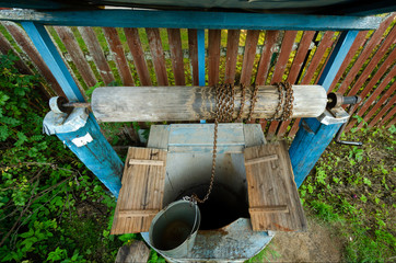 Village well with a reel. The doors of the well are open. At the well is a bucket filled with water.