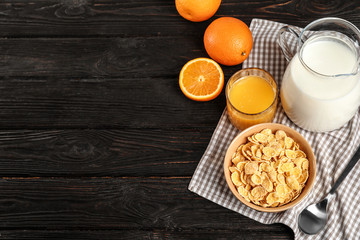 Bowl with healthy cornflakes for breakfast served on dark table. Space for text