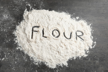 Word written on flour scattered over table, top view