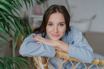 Attractive young woman with dark hair, nice make up looks directly at camera, leans on back of wicker furniture, domestic atmosphere, green plant, has confident expression. People and rest concept