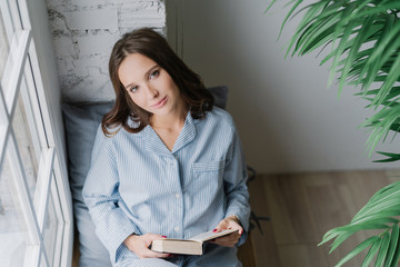 Top view of relaxed pleasant looking woman enjoys reading book, dressed in casual domestic suit, sits on window sill for good light and vision, enjoys loneliness and spare time. Hobby concept