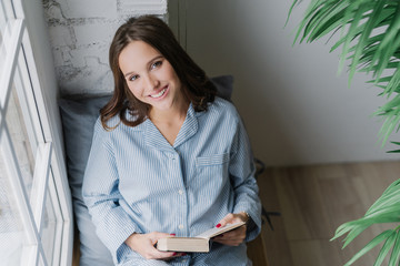 Photo of cheerful woman reads romantic story, holds book, wears casual clothes, poses on window sill in cozy room. View from above. Satisfied female model being in good mood, reads textbook.