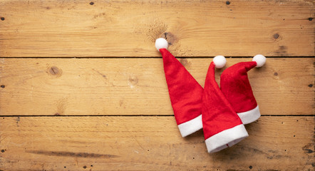 three red Santa Claus hats with wooden background