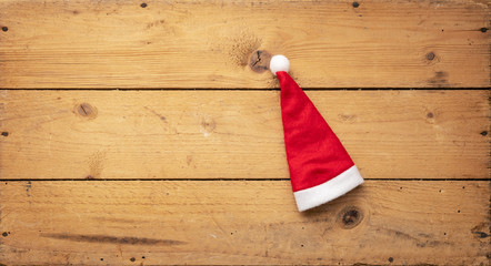 red Santa Claus hat with wooden background