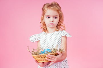 little blonde child with a chick cock easter in studio pink background.beautiful girl kid celebrating Easter Holiday with pets, painted eggs in wicker basket.dream birthday present