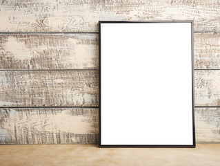 Mock up of an empty frame poster on a wall of wooden boards. Place for your design. Copy space