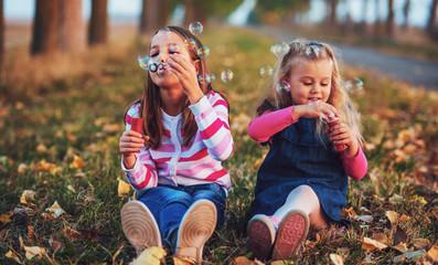 Childhood time. Cute little girls makes a soap bubbles Fototapete