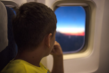 boy looking aerial view of sky and cloud outside airplane window