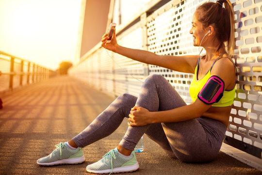 Female runner resting after running on bridge, taking selfie with mobile phone