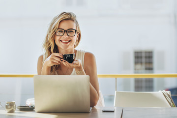 Businesswoman having coffee at coffeeshop