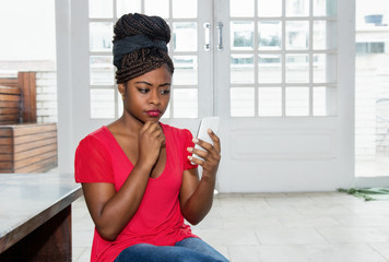 Thinking african american woman with mobile phone