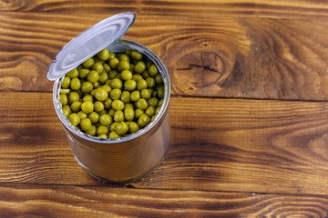 Open tin can of green peas on wooden table