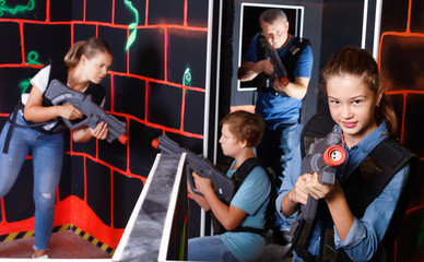 Portrait of teenager girl with laser gun having fun with her family on lasertag arena