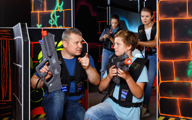 Happy teen boy with laser gun having fun on lasertag arena with his father