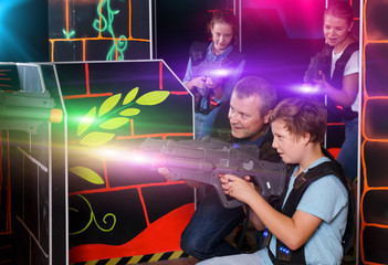 Cheery boy and his father aiming laser guns
