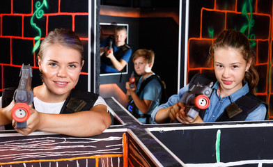 Modern young woman and teen girl with laser pistols playing laser tag in dark labyrinth