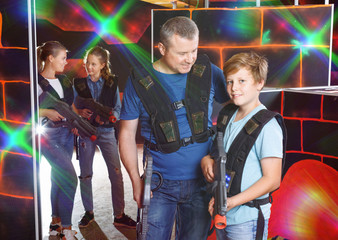 Portrait of teen boy and his father standing indoors with laser