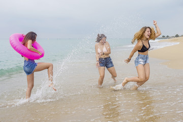 Group of female teenagers walking and enjoying on a beach sand