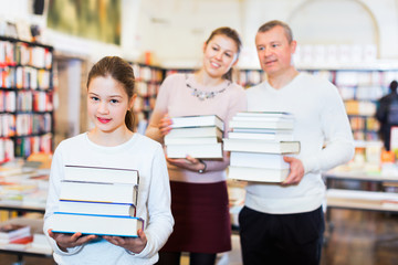Cheerful preteen girl and her parents holding piles of books bought in bookstore