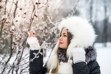 Young attractive woman in winter park with tree branches