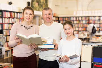 Adult family with daughter holding pile of books