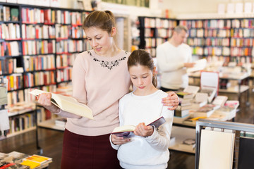 Woman with daughter looking for books in library