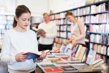 Girl choosing book with parents
