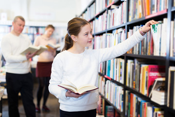 girl searching for textbooks on bookshelves