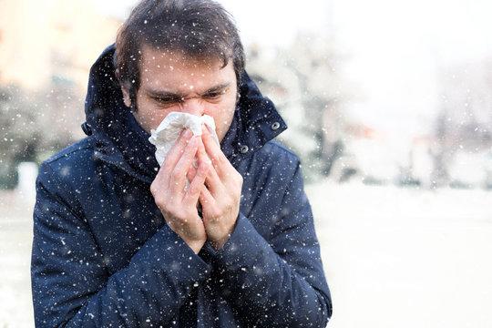 Sick man sneezing in the kleenex in winter