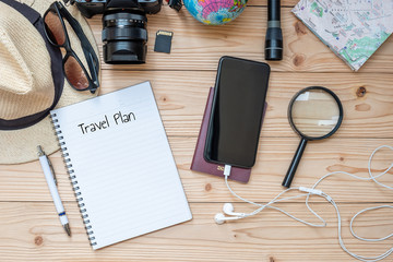 Travel planning concept background. Traveler's accessories; Map, Camera, Passport, Flashlight, Magnifying, smart Phone, Sunglasses, Hat and Notebook with Pen on wooden table, Top view and copy space
