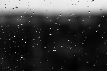 Rain drops on window with blured background in black and white.