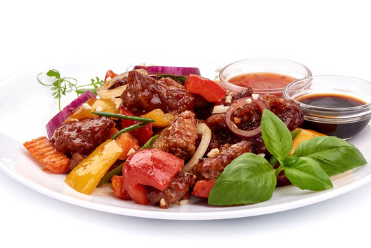 Roast Sweet and Sour Pork with vegetables in a plate with sauces, Chinese recipes WOK. Isolated on white background
