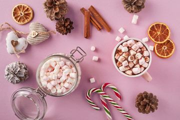 Top view of marshmallows in mug, glass jar and Christmas decoration on pink background
