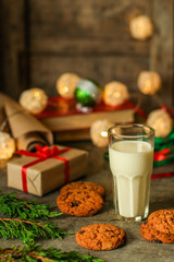 glass of milk and cookies, new year gifts. a cup on the table and a festive atmosphere. top view.