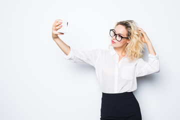 Portrait of young business woman making selfie photo on isolated white background