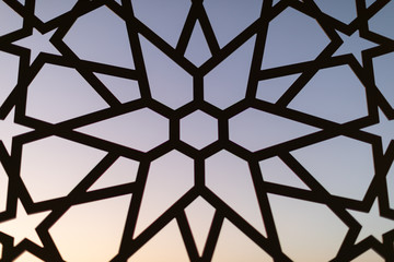 Fence with a floral pattern and stars at sunset. Oriental patterns. Turkish patterns and backgrounds