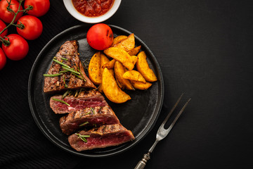 Delicious beef steak with salad, aromatic herbs, chery tomatoes and potatoes