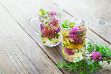 Two glass mugs of healthy herbal tea with medicinal herbs with copy space.