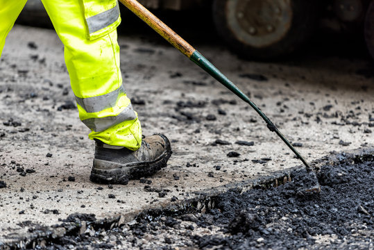 Closeup of construction worker with neon yellow green pants clothing, boots, raking hot black wet tar and asphalt, bitumen in city London