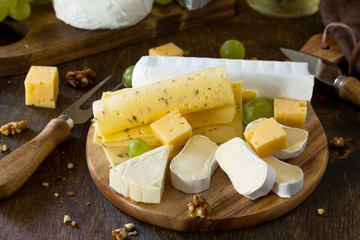 Cheese plate. Assortment of cheeses, grapes and nuts on dark rustic wooden table.