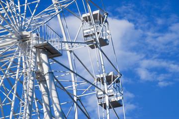 White ferris wheel against the blue sky. Ferris wheel in the park.