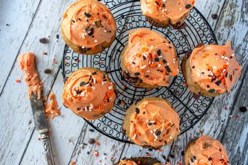 Orange and black pumpkin cupcakes with Halloween sprinkles