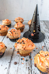 Orange and black pumpkin cupcakes with Halloween sprinkles