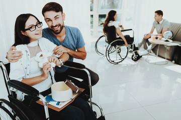 Man Gives Small Plush Bear Woman in Wheelchair.