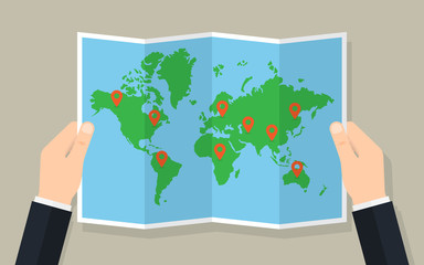Stores à enrouleur Carte du monde Hands hold folded paper map of world with markers