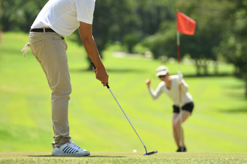 Man and woman playing golf on a beautiful natural golf course