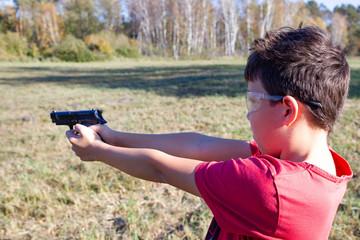 Gun in a hand, boy shooting air gun.